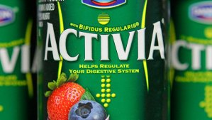 "Close up of a 4-ounce Activia container, which advertises its trademark named bacterial strain, bfidius regularis. The container also includes the product's health claim, ""Helps regulate your digestive system."" The curving vertical lines mimic the female abdomen included in Activia television commercials."